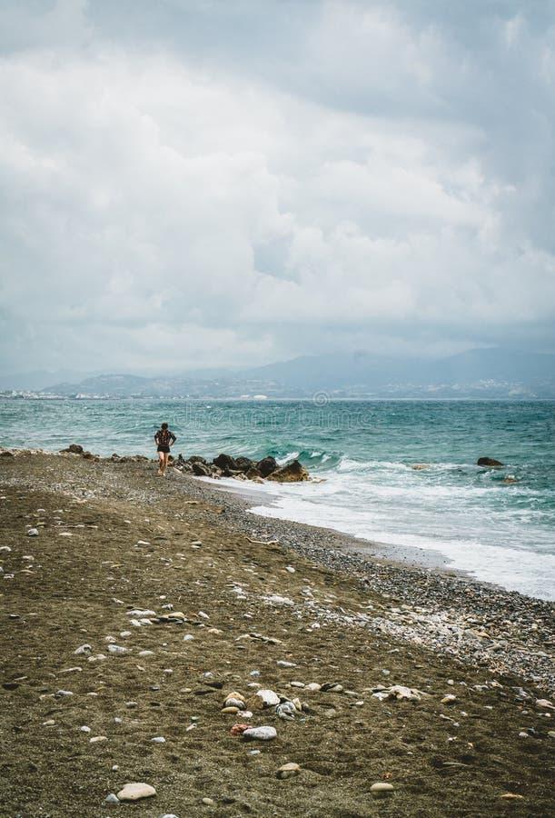 Typische strandscène in eiland Kreta Jonge niet geïdentificeerde vrouw die langs het strand loopt Mening naar oceaan met stock foto
