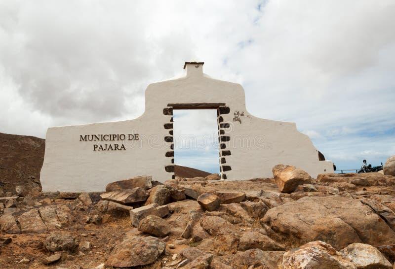 Typische witte de boogpoort van het gemeenteteken dichtbij Pajara met het landschap van de woestijnberg op de achtergrond, Fuerte royalty-vrije stock foto's