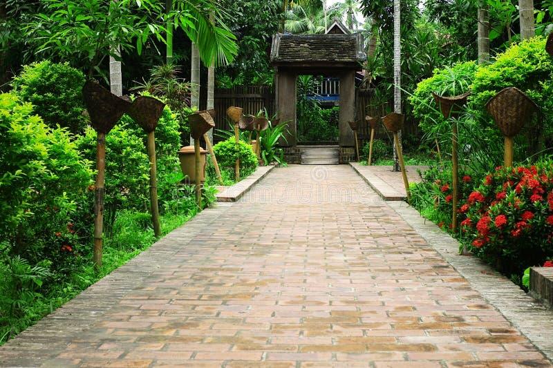 typische zuidoostaziatische tuin met weelderige vegetatie met een oude poort en toortsen langs de bestrating stock fotografie