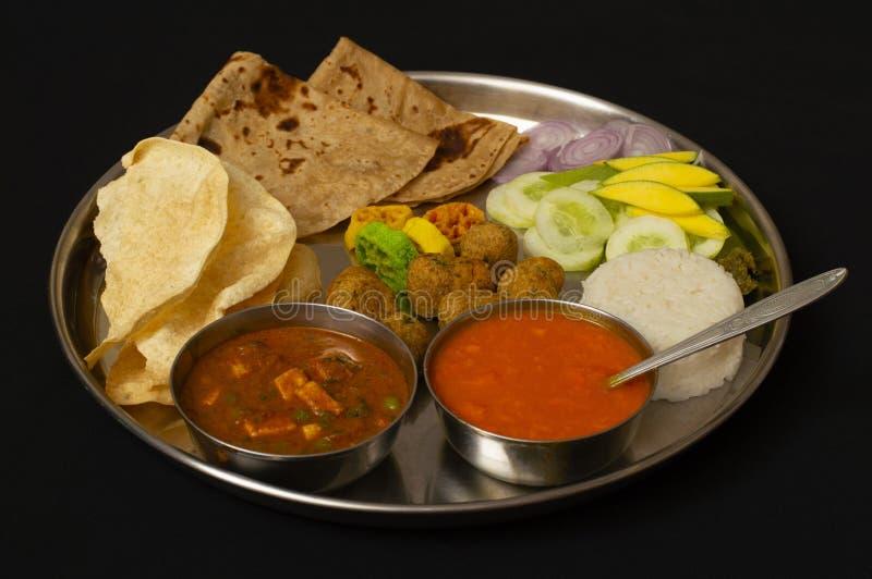 Typischer Maharashtrain-Mittagessenteller mit Chapati, Mango Saft oder aamras, Reis, Zwiebel und Gemüse lizenzfreies stockbild