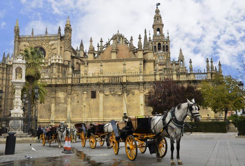 Typisches Bild mit Pferdewagen und der Kathedrale von Sevilla stockbilder