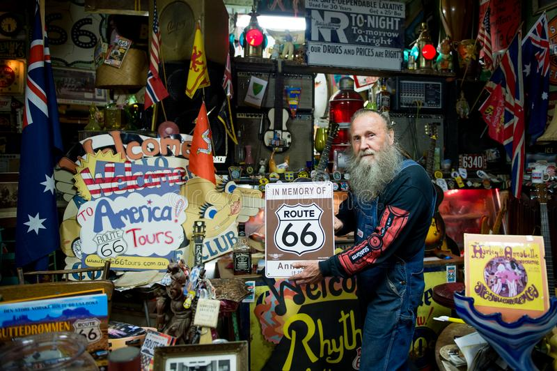 Typisches Gesicht eines alten Amerikaners auf Route 66, das mit dem Route 66 -Zeichen aufwirft lizenzfreies stockbild