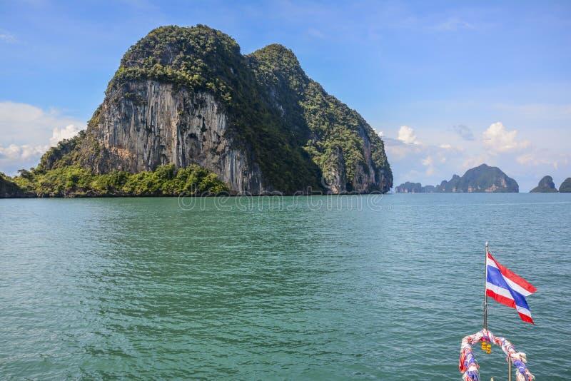Typisches Thailand-Bild: Klippen im Meer mit der thailändischen Flagge lizenzfreies stockfoto