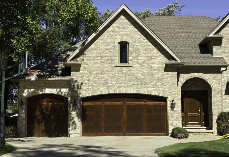 Typisk amerikanskt hus med garage för två dörr royaltyfri bild
