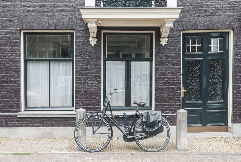 Typisk Amsterdam gatasikt i Nederländerna med den gamla dörrar och fönster och tappningcykeln royaltyfri fotografi