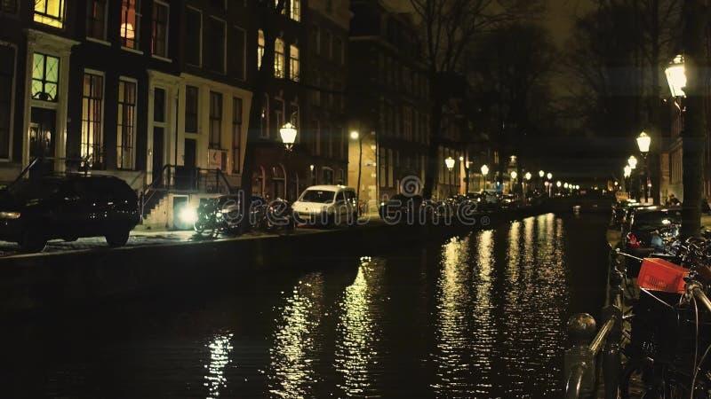 Typisk Amsterdam kanal och för hus invallning tillsammans med på natten, Nederländerna arkivfoto