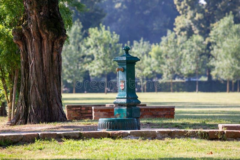 Typisk drakes springbrunn för vatten för huvudgräsplan med fritt drickbart vatten av staden av Milan, med Röda korsetsityemblemet arkivbild