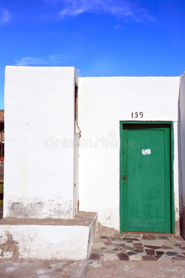 Typisk fasad av en boning på Lanzarote, med vita väggar och den gröna dörren arkivbild