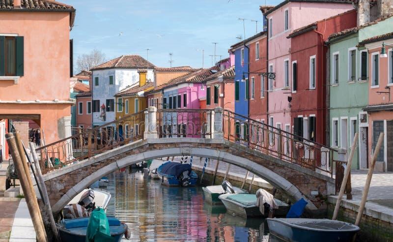 Typisk gataplats som visar den brighly målade hus och bron över kanalen på ön av Burano, Venedig arkivfoto