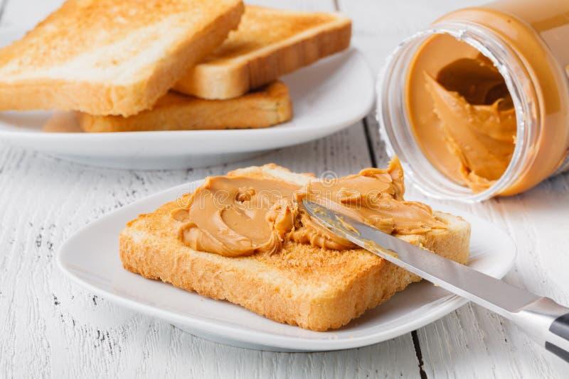 Typisk hög-kalori frukost med rostat bröd- och jordnötsmör royaltyfri foto
