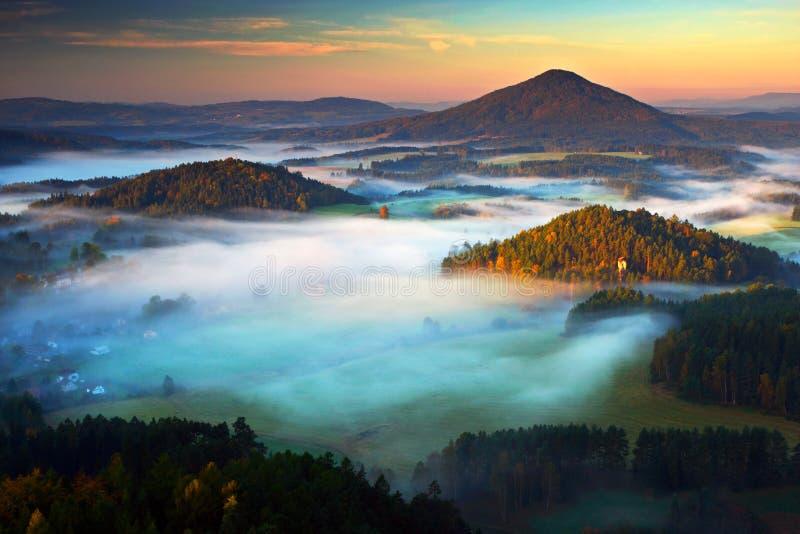 Typisk höstlandskap för tjeck Kullar och byar med dimmig morgon Morgonnedgångdalen av bohemmet Schweiz parkerar Kulleintelligens royaltyfria bilder
