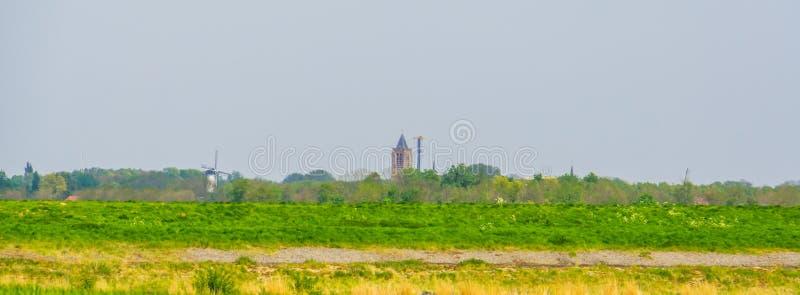 Typisk holländskt grönt landskap med en kyrka och väderkvarnar, horisont Tholen, Zeeland, det nederländskt arkivfoto