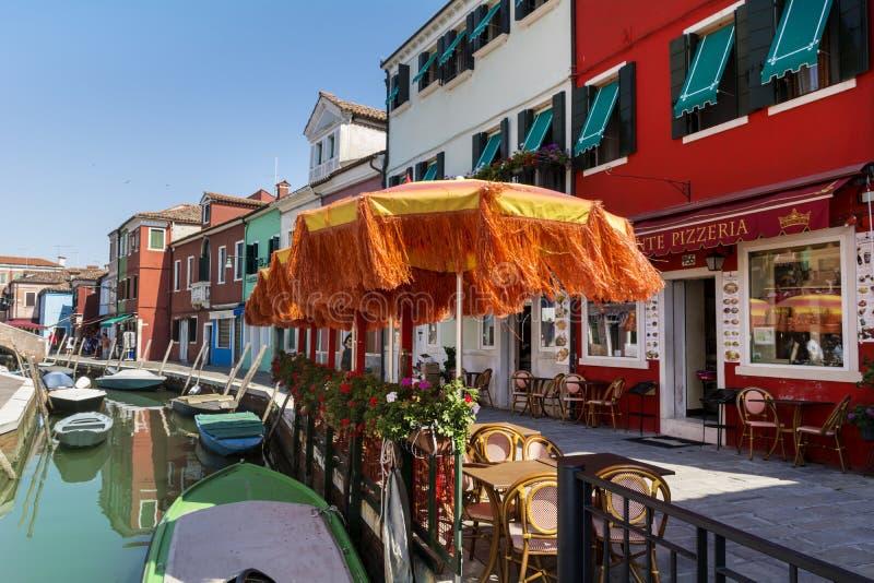 Typisk italiensk stång med stora orange paraplyer royaltyfri fotografi