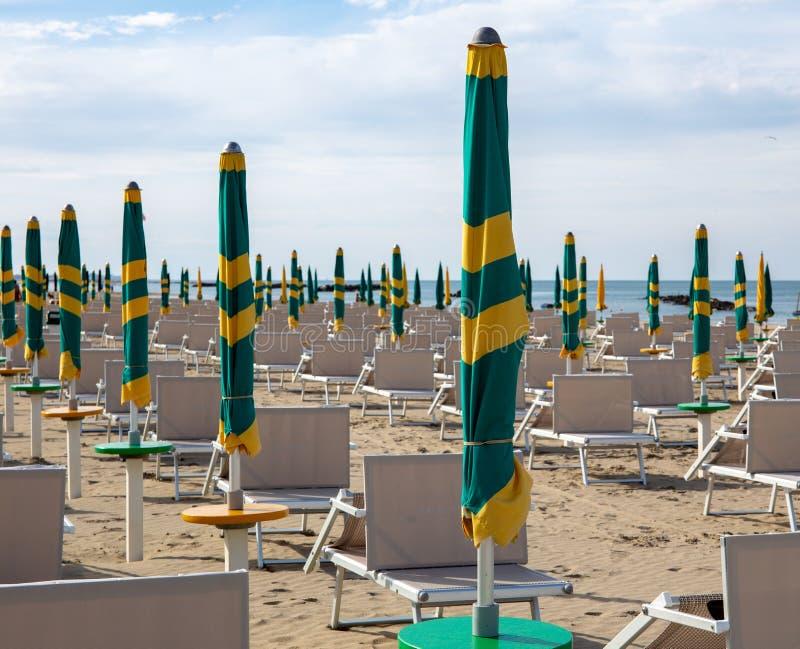 Typisk italiensk strand i det Riviera Romagnola omr?det, Riminien eller Riccionen: gr?na och gula paraplyer som st?ngs fortfarand arkivbilder