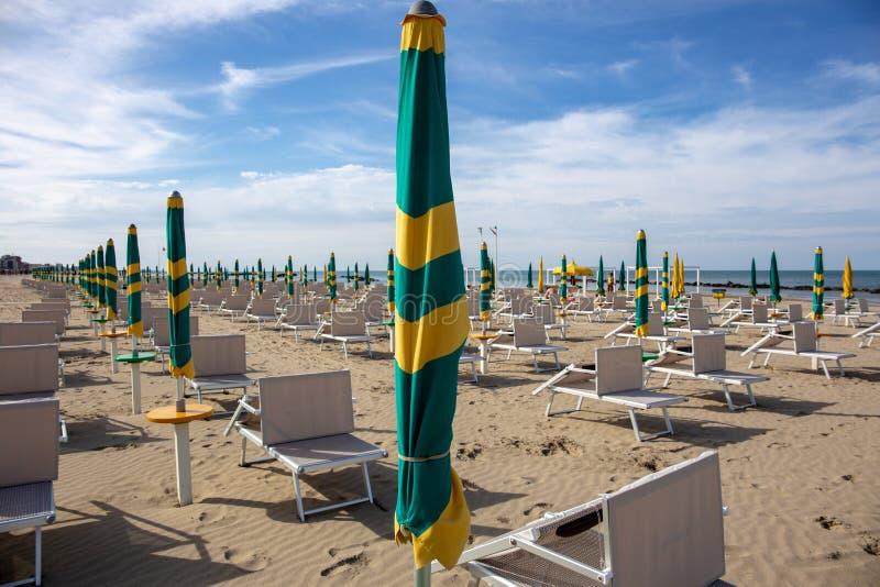 Typisk italiensk strand i det Riviera Romagnola omr?det, Riminien eller Riccionen: gr?na och gula paraplyer som st?ngs fortfarand royaltyfri bild