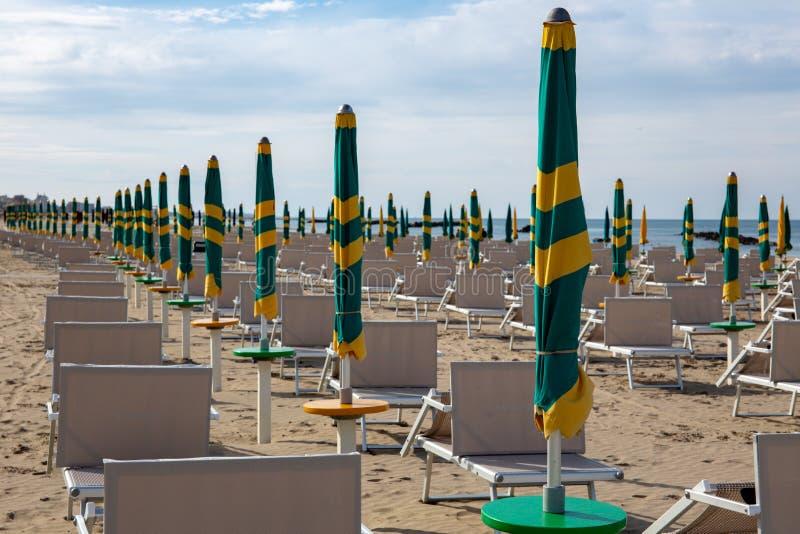 Typisk italiensk strand i det Riviera Romagnola omr?det, Riminien eller Riccionen: gr?na och gula paraplyer som st?ngs fortfarand arkivfoton