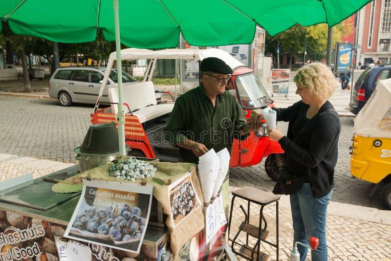 Typisk kastanjebrun försäljare i gatorna av Lissabon royaltyfria foton