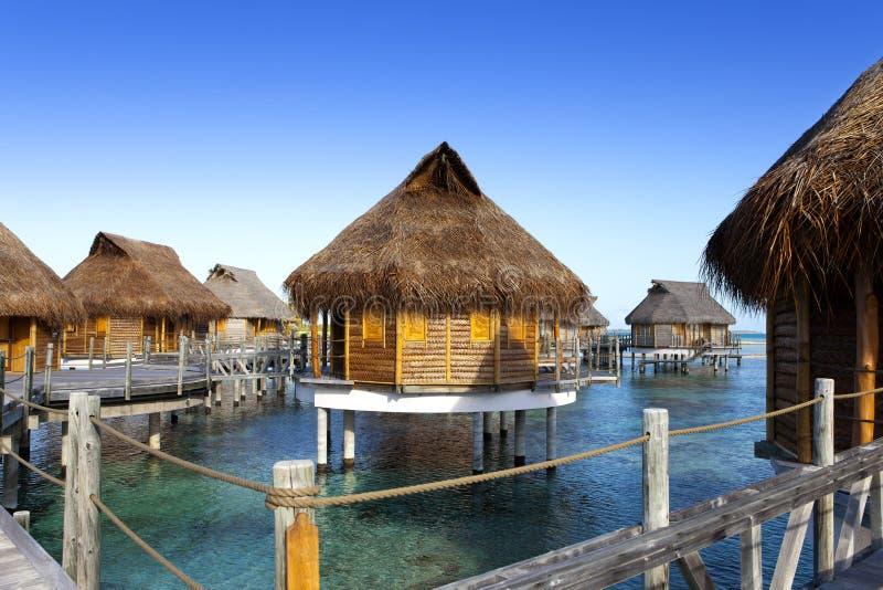 Typisk landskap av tropiska öar - kojor, trähus över vatten royaltyfri fotografi