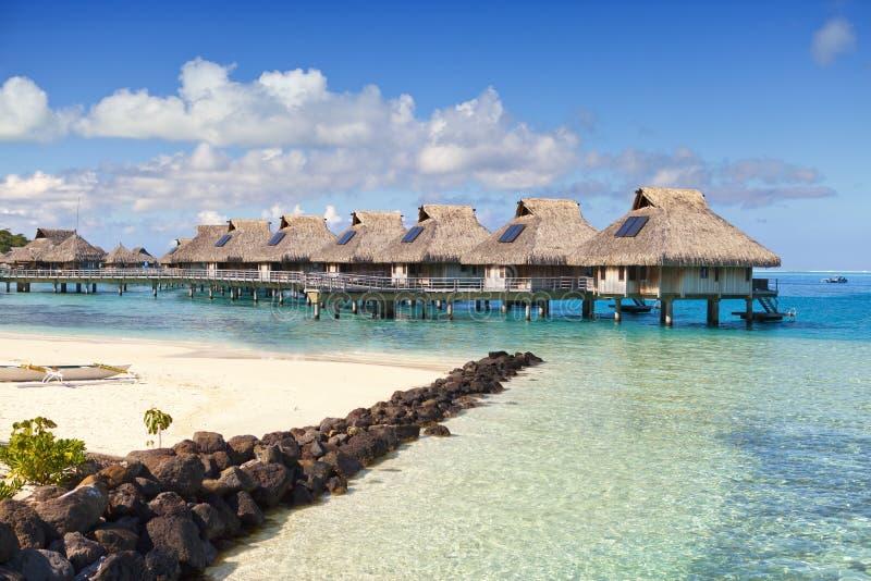 Typisk landskap av tropiska öar - kojor, trähus över vatten royaltyfri bild