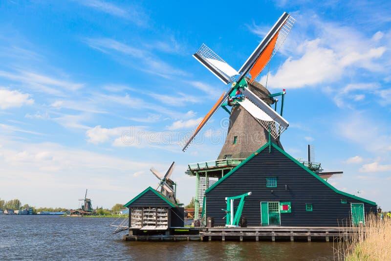 Typisk landskap för holländare Traditionella gamla holländska väderkvarnar mot blå molnig himmel i den Zaanse Schans byn, Nederlä arkivfoto