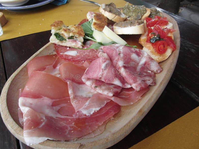 Typisk lantlig tuscan aptitretare med crostinien, prosciutto, muskler, salami, ost på ett trämagasin italiensk startknapp royaltyfri foto