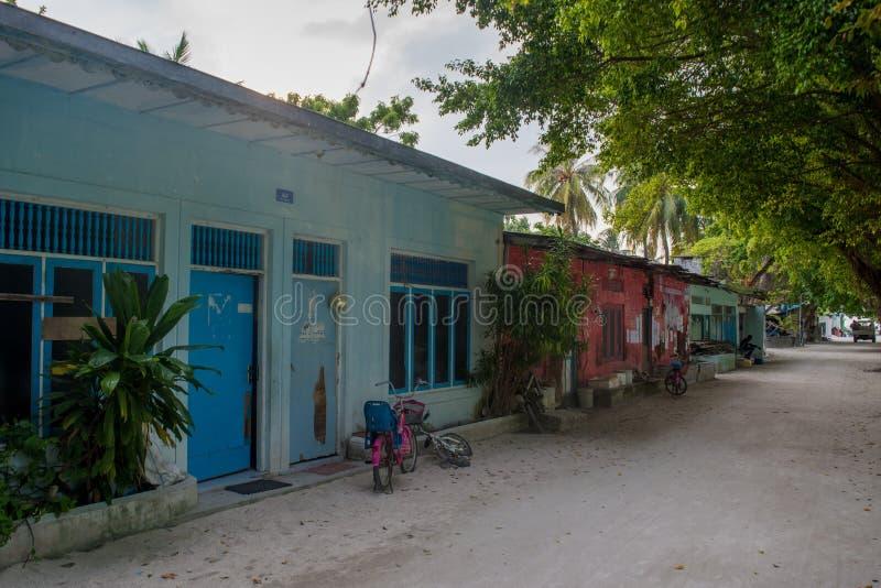 Typisk lokal gata med små hus och träd på den Fenfushi ön fotografering för bildbyråer