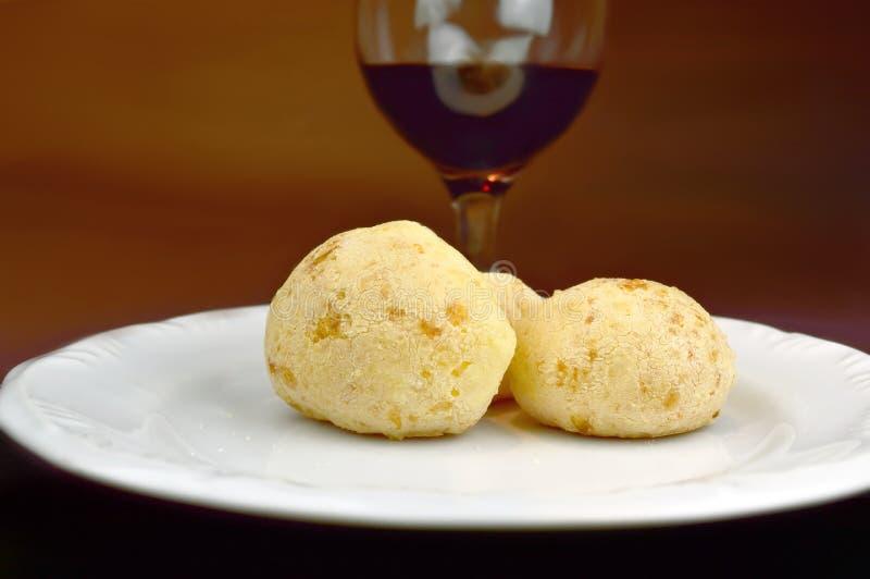 Typisk mat för ostbrödbrasilian från Minas Gerais som är bekant som Pao de Queijo och vin arkivfoto