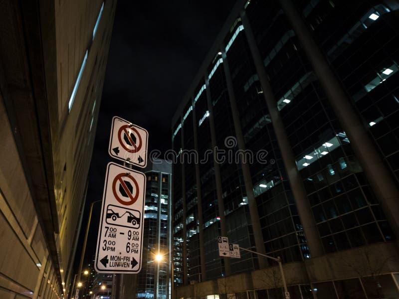 Typisk norr - paking för amerikan och inget parkera tecken med detaljanvisningar på den parkera reglementet som tas på natten i O royaltyfria foton