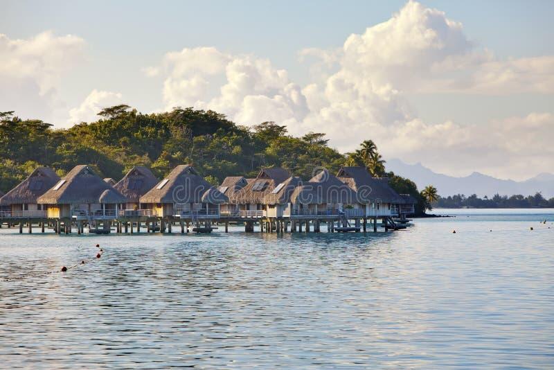 Typisk Polynesian landskap - ö med palmträd och små hus på vatten i havet och bergen på en bakgrund arkivfoto