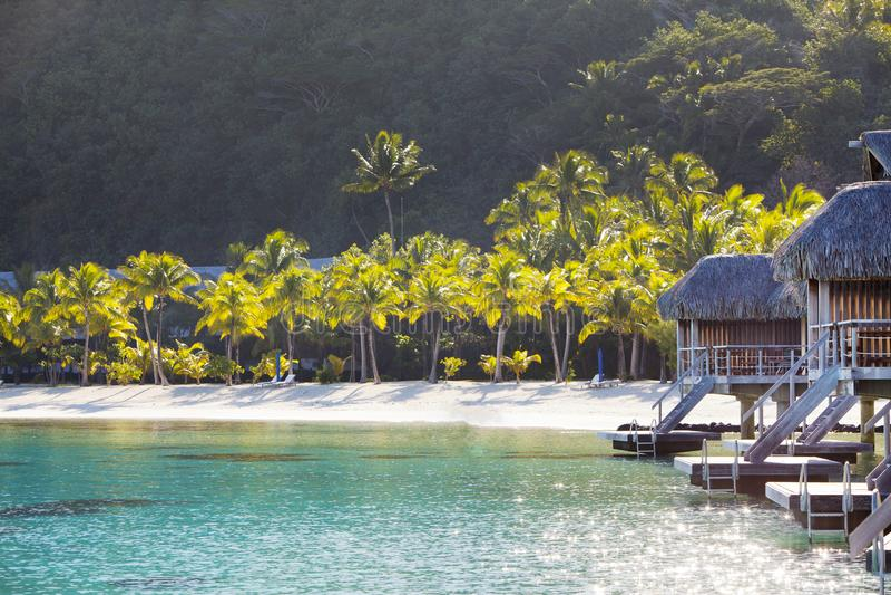 Typisk Polynesian landskap - ö med palmträd och små hus på vatten i havet och bergen på en bakgrund royaltyfria bilder