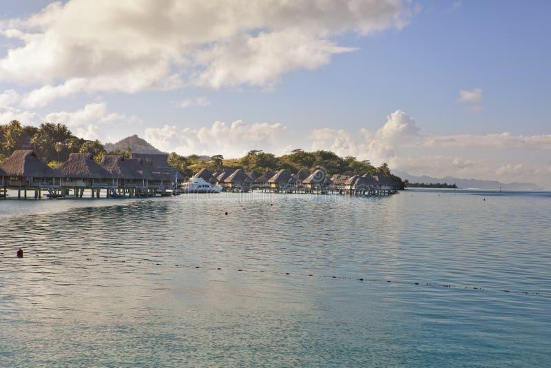 Typisk Polynesian landskap - ö med palmträd och små hus på vatten i havet och bergen på en bakgrund royaltyfria foton