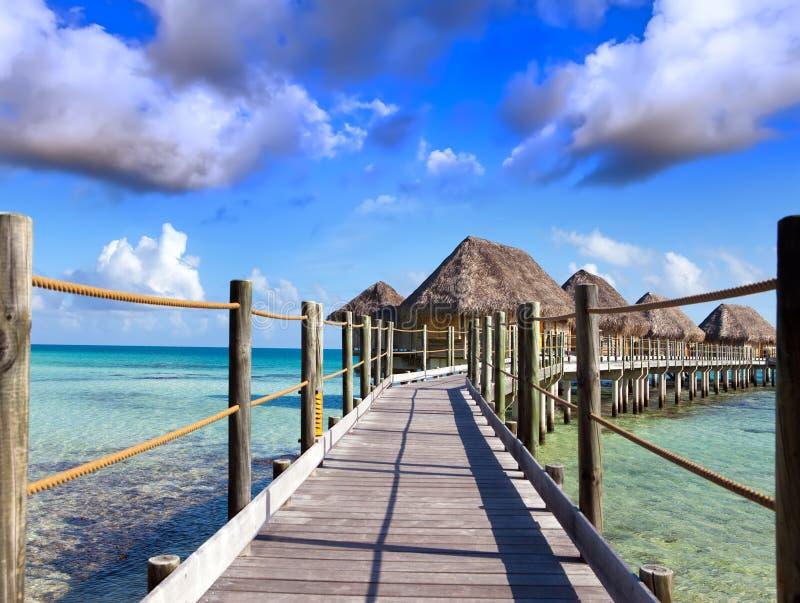 Typisk Polynesian landskap - små hus på vatten royaltyfria bilder