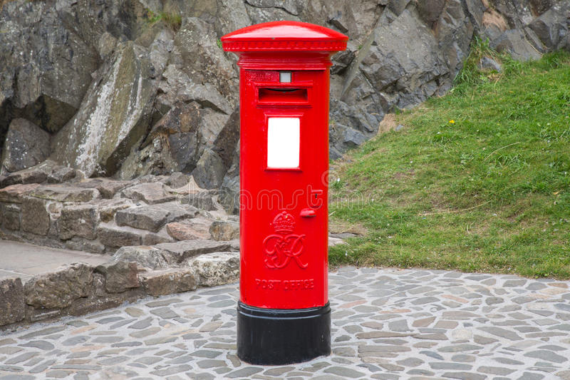 Typisk röd brittisk postbox royaltyfri foto
