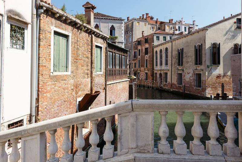 Typisk sikt av en kanal från en peshmoist med baluster, Venedig, Italien arkivfoto