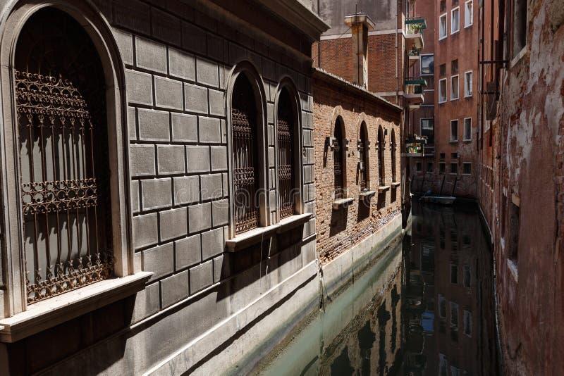 Typisk sikt av en kanal av Venedig Mycket smalt avstånd mellan byggnader royaltyfri bild
