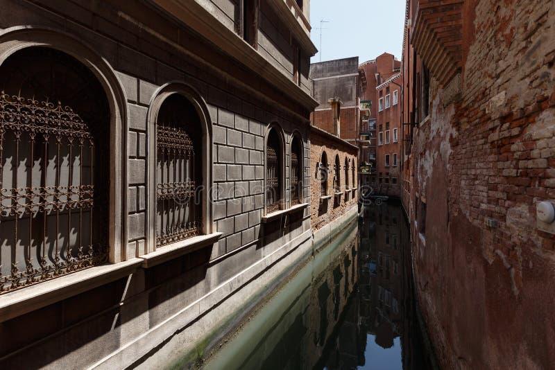 Typisk sikt av en kanal av Venedig Mycket smalt avstånd mellan byggnader royaltyfria foton