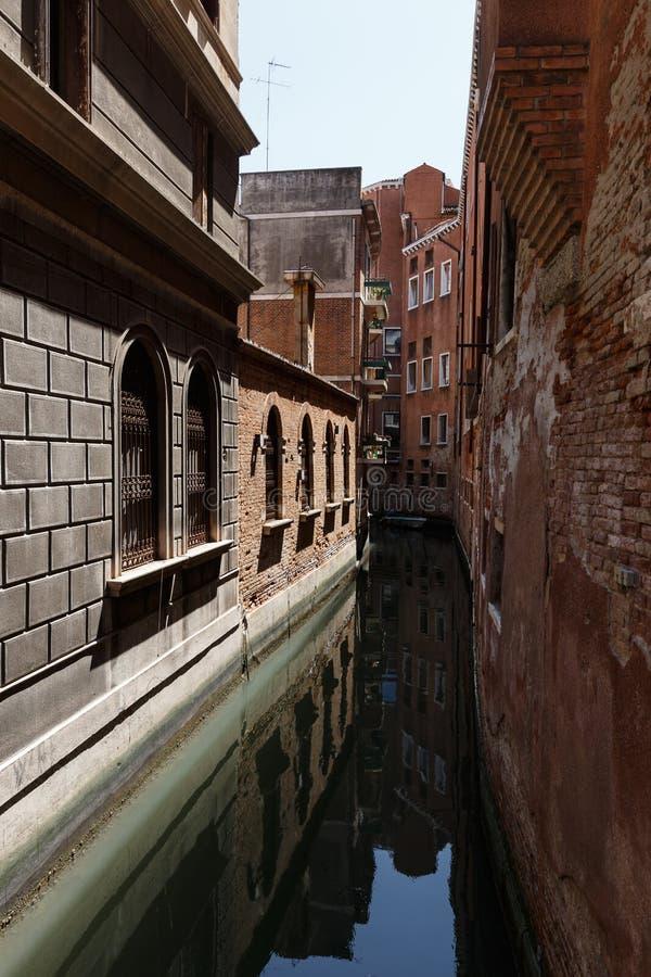 Typisk sikt av en kanal av Venedig Mycket smalt avstånd mellan byggnader arkivbilder
