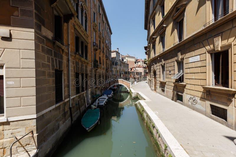 Typisk sikt av fartyg och gondoler under den mycket lilla bron på kanalen av Venedig royaltyfri fotografi