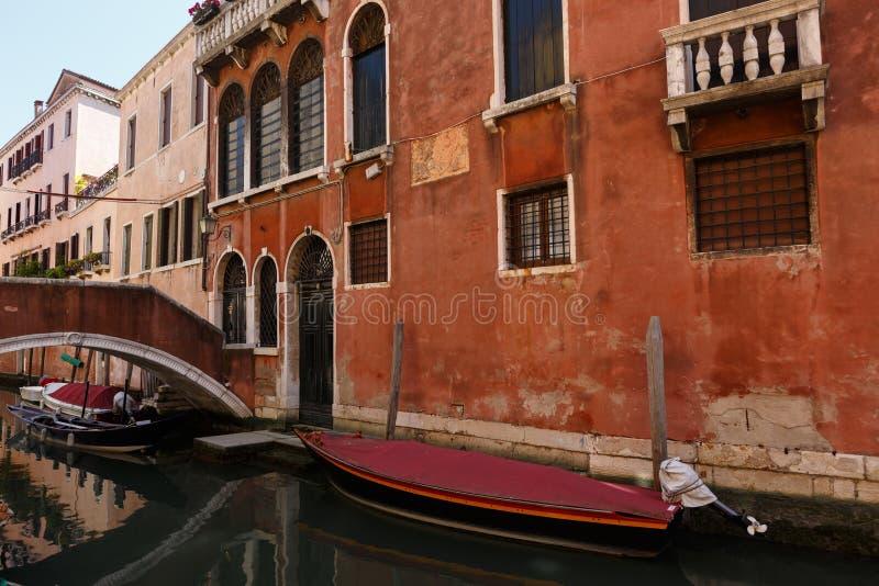 Typisk sikt av fartyg och gondoler under den mycket lilla bron på kanalen av Venedig royaltyfri bild