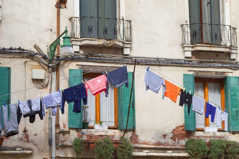 Typisk sikt; gatorna av Venedig; tvättad kläder som torkar på kablar utanför byggnaden, Venedig, Italien Co arkivbild