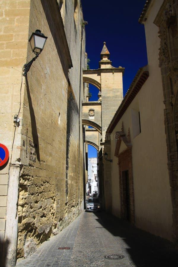 Typisk smal bakgata med bågar som kontrasterar med mörkt - blå himmel i traditionell byArcos da la Frontera i landskap arkivbilder