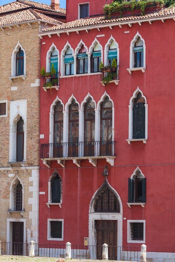 Typisk venetian byggnad, röda väggar med vita gotiska fönster arkivfoton