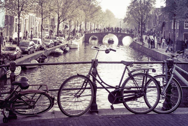 Typiska Amsterdam cyklar, broar & kanaler arkivbild