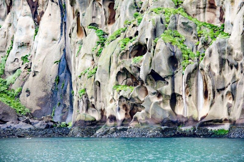 Typiska basaltklippor med grottor för seabirds över turkoshavet på Heimaey, Island royaltyfria bilder