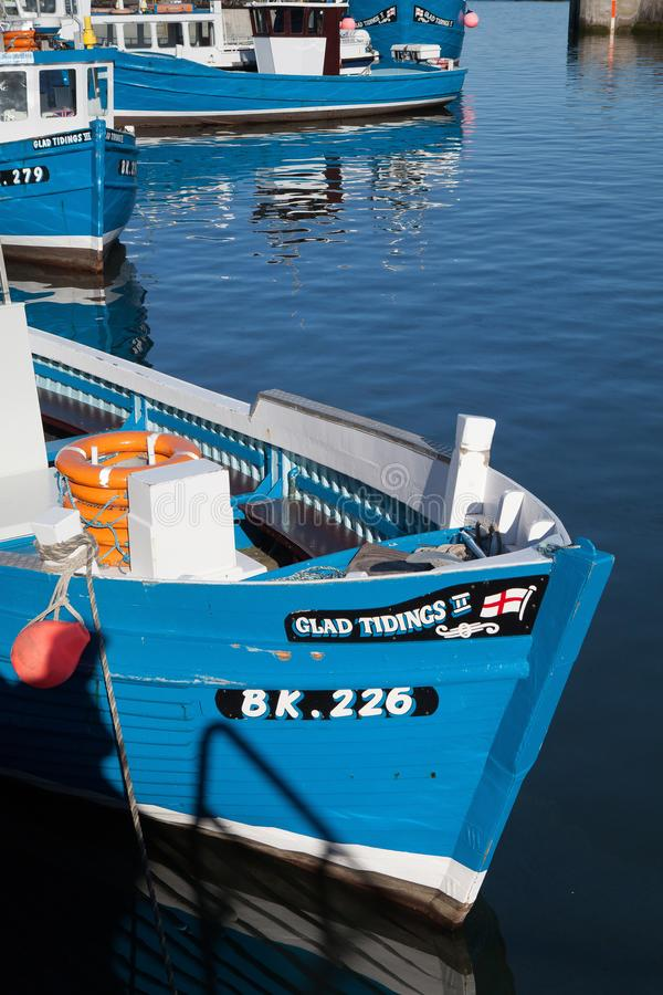 Typiska blåa fiskebåtar i den Seahouses hamnen arkivbild