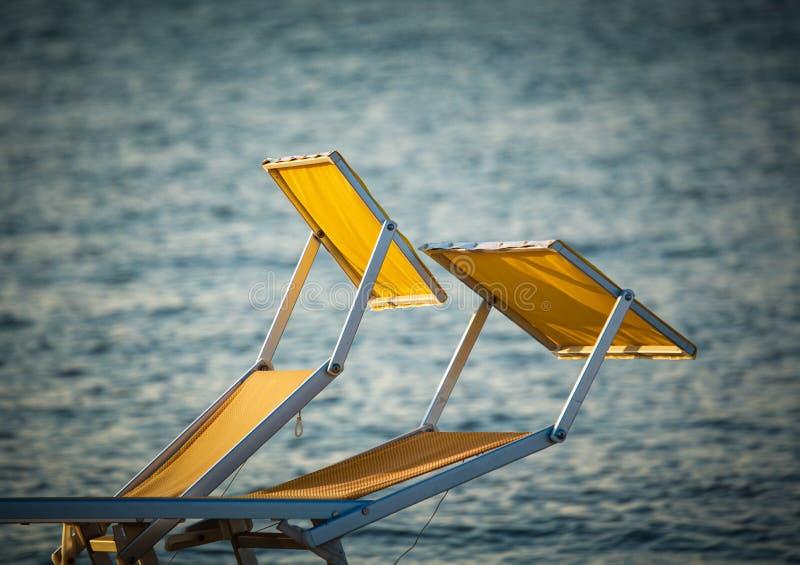 Typiska gula eller orange sunbeds av den Riviera Romagnola Adriatiska havet kusten av Italien, med havet i bakgrunden Rimini stra arkivbilder