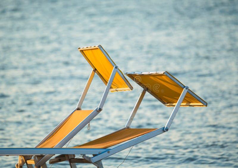 Typiska gula eller orange sunbeds av den Riviera Romagnola Adriatiska havet kusten av Italien, med havet i bakgrunden Rimini stra royaltyfri foto