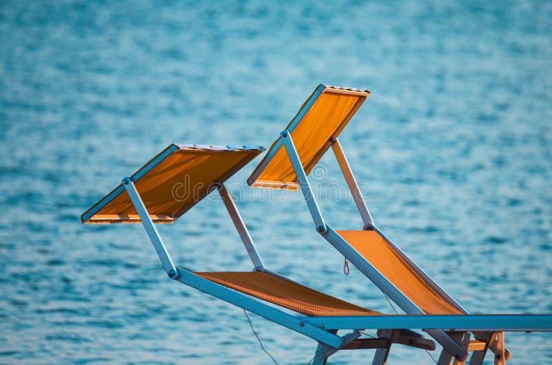 Typiska gula eller orange sunbeds av den Riviera Romagnola Adriatiska havet kusten av Italien, med havet i bakgrunden Rimini stra arkivbild