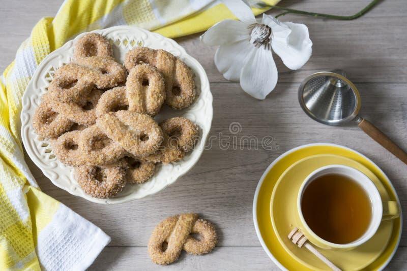 Typiska kakor från Nederländerna kallade Krakeling, med kopp te och blomman royaltyfri fotografi
