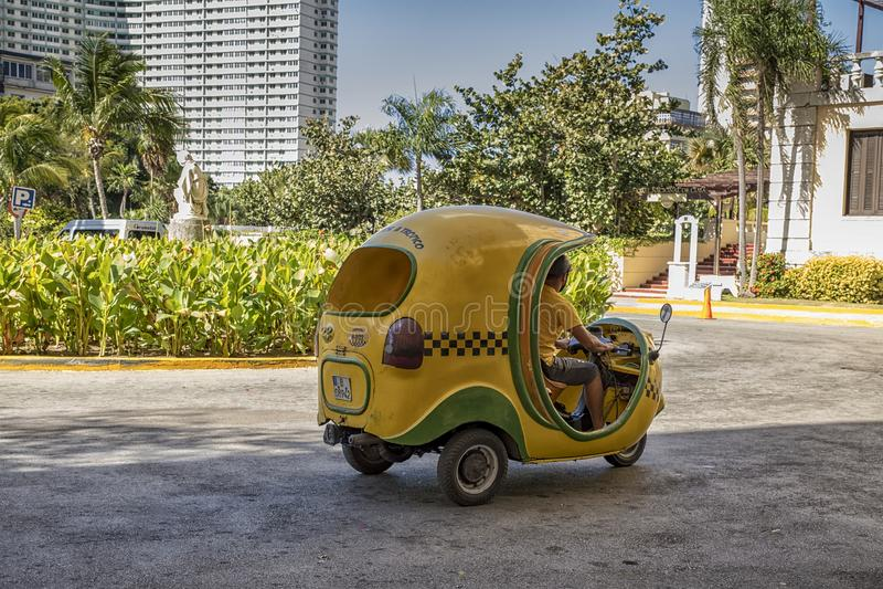 Typiska kubanska mopedtaxi är bekanta som Cocotaxien arkivfoto